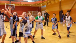 boys playing basketball in gymnasium